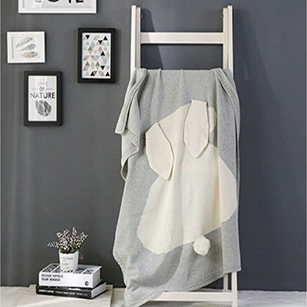 grey baby blanket with a white woven bunny rabbit shape and 3D ears and tail hanging on a small ladder in a kid's room.