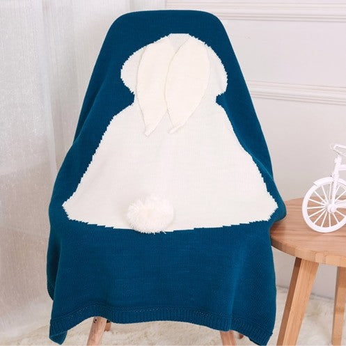 blue baby blanket with a white woven bunny rabbit shape, 3D ears, and 3D tail hanging on a chair in a kid's room.