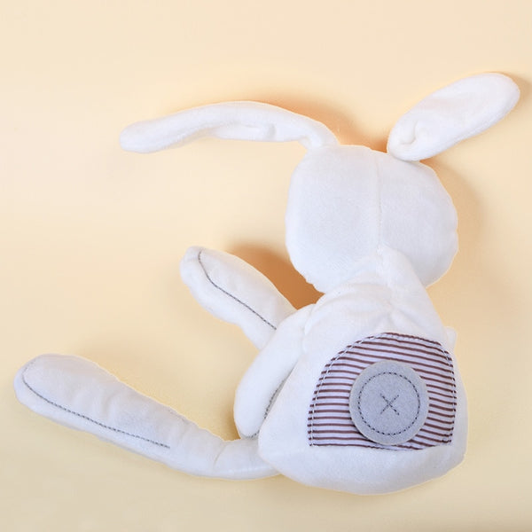 the back of a white stuffed baby bunny rabbit plush with a grey button and striped fabric sewn to the bottom of the bunny