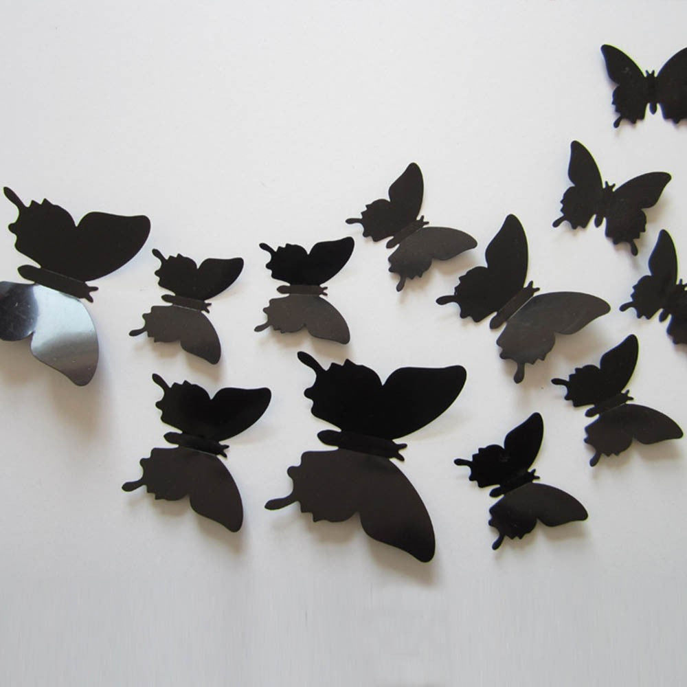 black plastic 3D decal butterflies in a variety of sizes attached to a wall