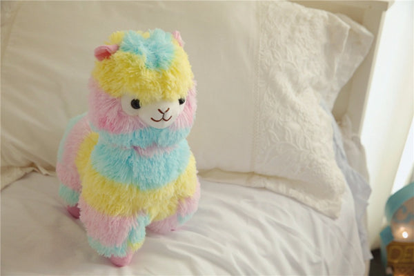 multi-colored rainbow stuffed alpaca plush with pale blue, yellow, and pink stripes in a kid's bedroom