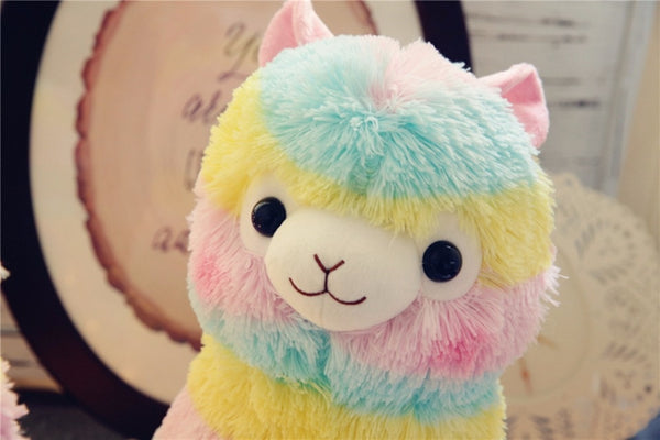 the face of a multi-colored rainbow stuffed alpaca plush with pale blue, yellow, and pink stripes in a kid's bedroom