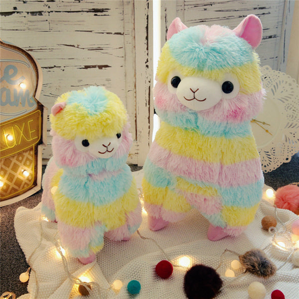 a small and large multi-colored rainbow stuffed alpaca plush with pale blue, yellow, and pink stripes