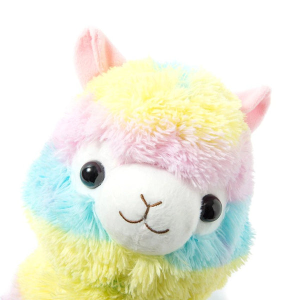 the face of a multi-colored rainbow stuffed alpaca plush with pale blue, yellow, and pink stripes