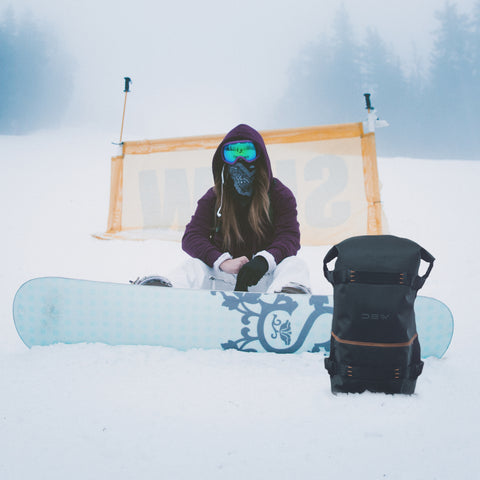 Girl sitting with her snowboard in the snow next to her DEW backpack