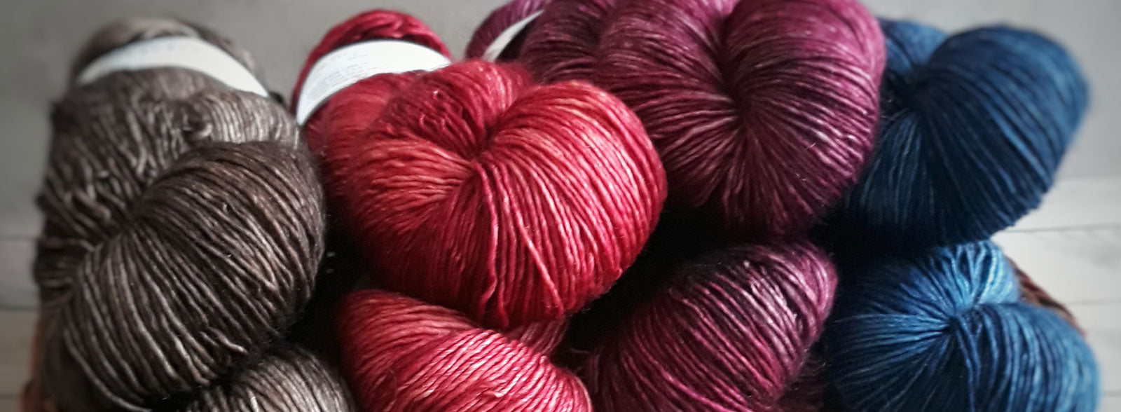 A photo of different coloured yarns in brown, red, crimson and blue. This link takes you to the all collections page.