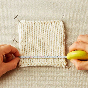 Cocoknits - Tape Measure - photo shows person measuring a knitted tension square using the Mustard Seed coloured tape measure | Yarn Worx