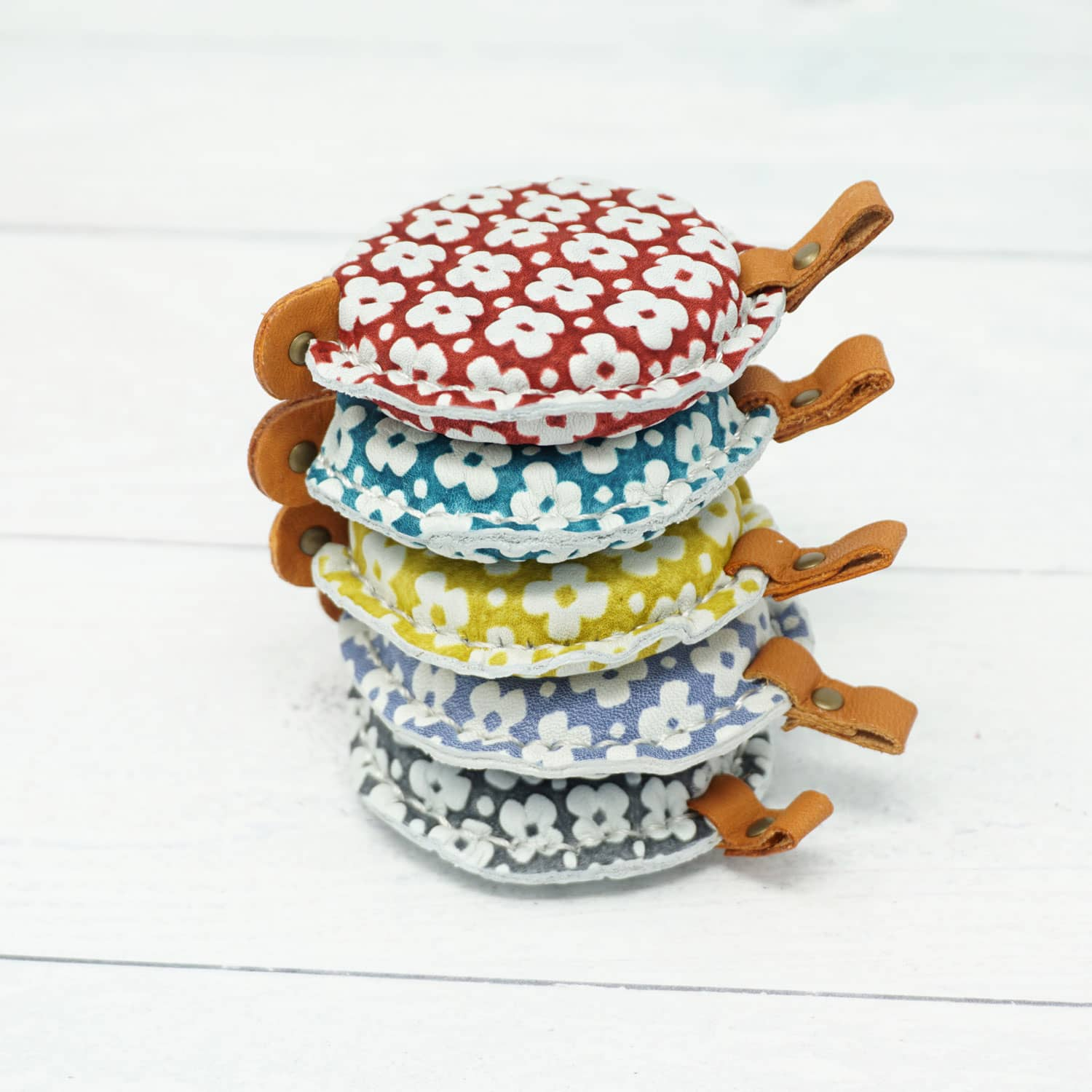Cohana Yuzen Leather Tape Measure shown in a stack - red, green, yellow, blue, grey | Yarn Worx