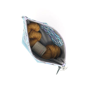 Beautiful Syster Hillary zipped project bag with mermaid scales design. Bag is shown open with a skein of yarn inside.