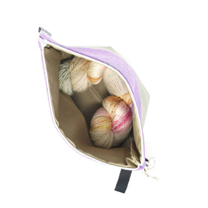 Beautiful Syster Hillary zipped project bag with beige and purple fabric. Bag is shown open with a skein of yarn inside.