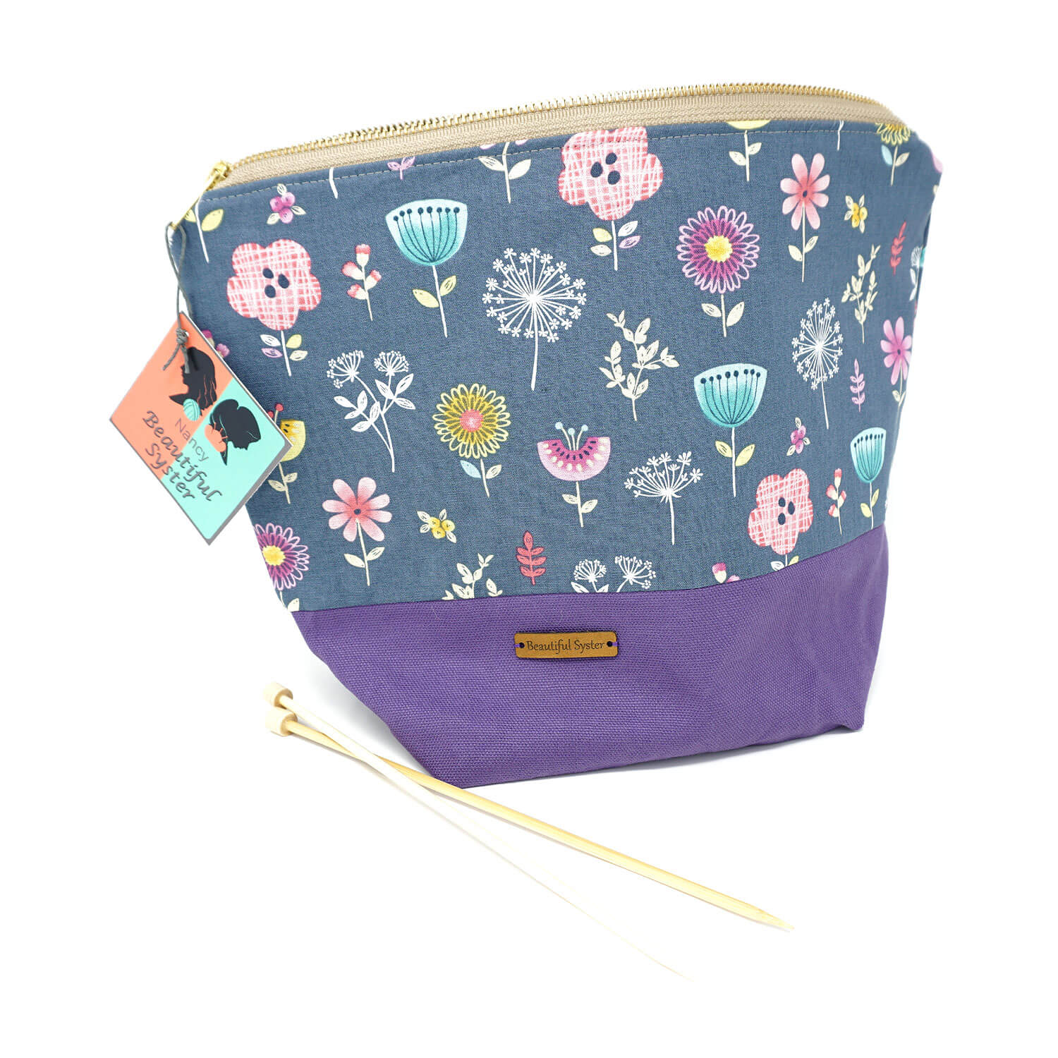 Beautiful Syster Nancy zipped project bag with flowers. Bag is stood up with a pair of knitting needles beside.