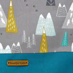 Beautiful Syster Nancy project bag with teal and grey with coloured mountains. Closeup of the front including the Beautiful Syster branding.