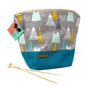 Beautiful Syster Nancy zipped project bag with teal and grey with coloured mountains. Bag is stood up with a pair of knitting needles beside.