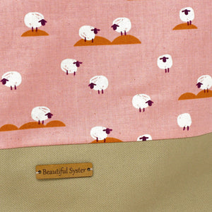 Beautiful Syster Nancy zipped project bag with white sheep and pink fabric. Image is a closeup of the leather tag.