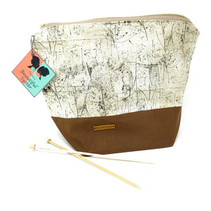 Beautiful Syster Nancy zipped project bag with brown and weathered wood effect fabric. Bag is stood up with a pair of knitting needles beside.