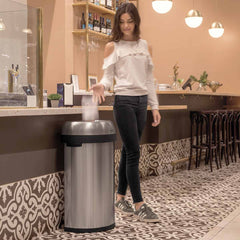 60L semi-round open can - brushed stainless steel - lifestyle woman in cafe throwing trash away