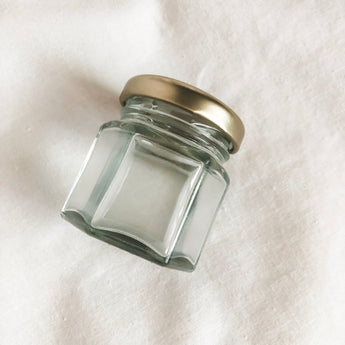 A small glass jar with a gold lid. The jar is resting on a white fabric background.