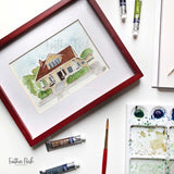 A craftsman style home painted in watercolor surrounded by tubes of watercolor paint on a white background.