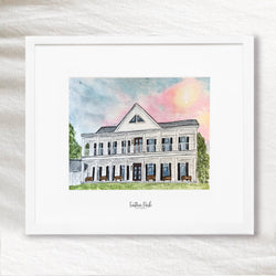 An image of a water color portrait of a home with a pink and blue sky. The painting is framed in a white frame with a white mat. Painted by Gina Sutton from Feather Park Lettering