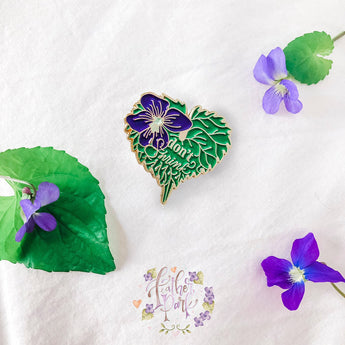 A gold enamel pin badge featuring a purple violet flower on a green violet leaf with the words