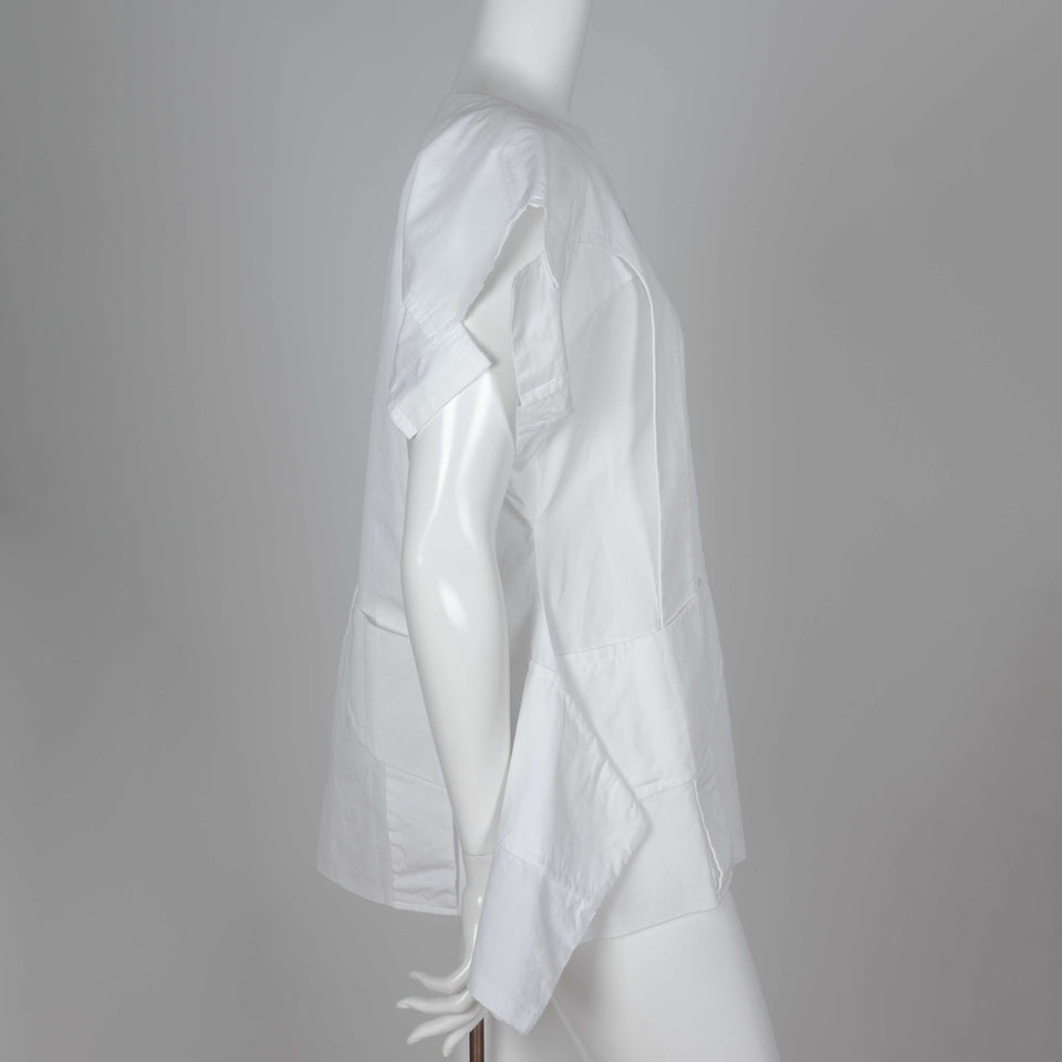 "Comme des Garçons 2014 white shirt called ""Flat Pack"" with overlapping layers of white cotton and an intriguing silhouette."