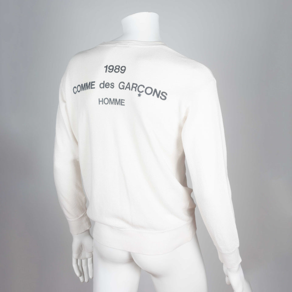 Comme des Garçons Homme 1989, a white long sleeve knit shirt with brand text on back.