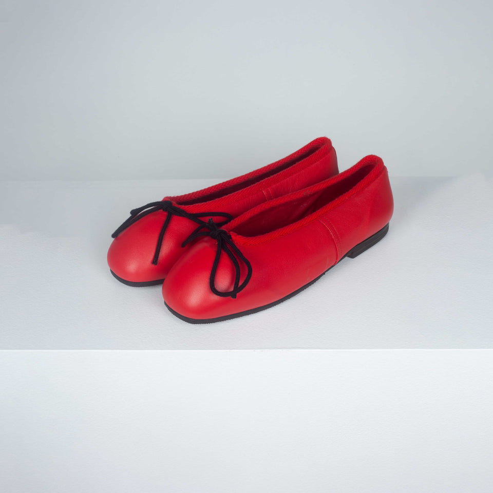 Comme des Garçons red leather ballet shoes with hard toe, black decorative bow and black slightly heeled soles.