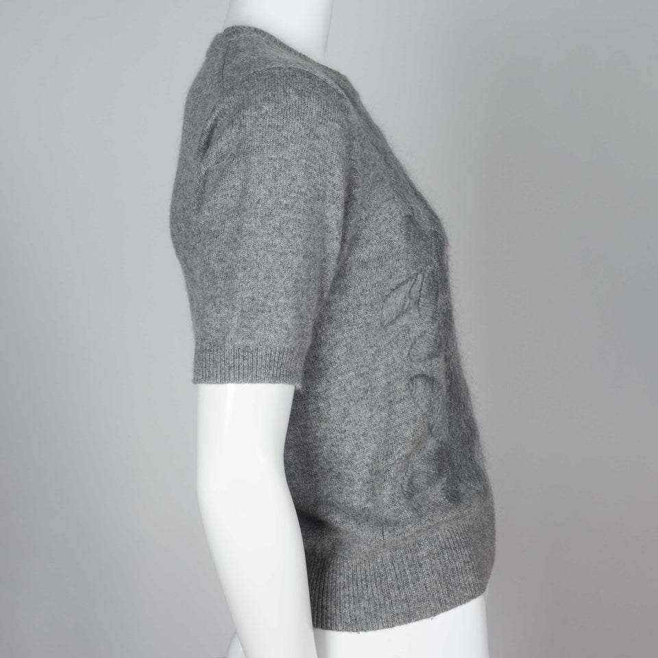 Comme des Garçons, a gray short sleeve sweater with silk embroidered flowers on front.