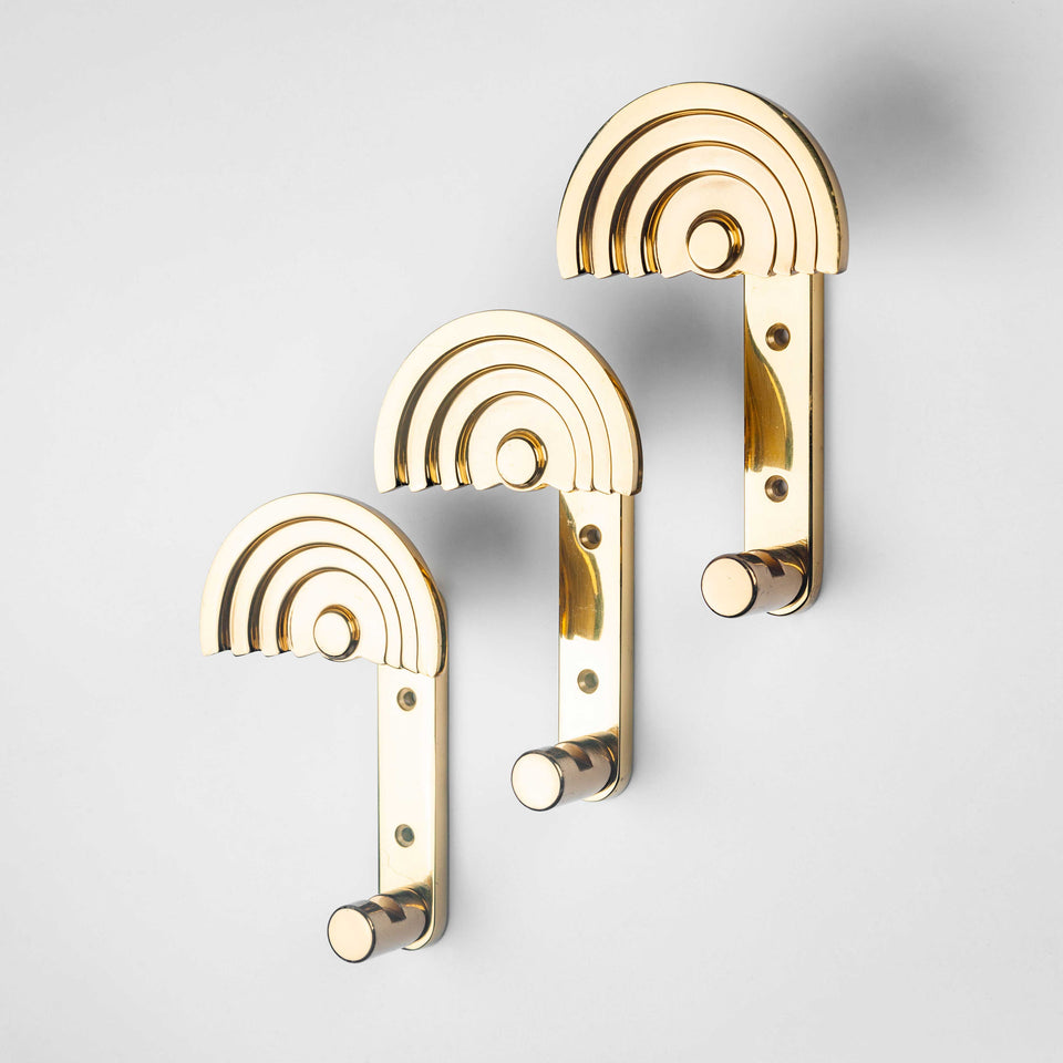 Architectural coat hooks in polished brass by Ettore Sottsass.