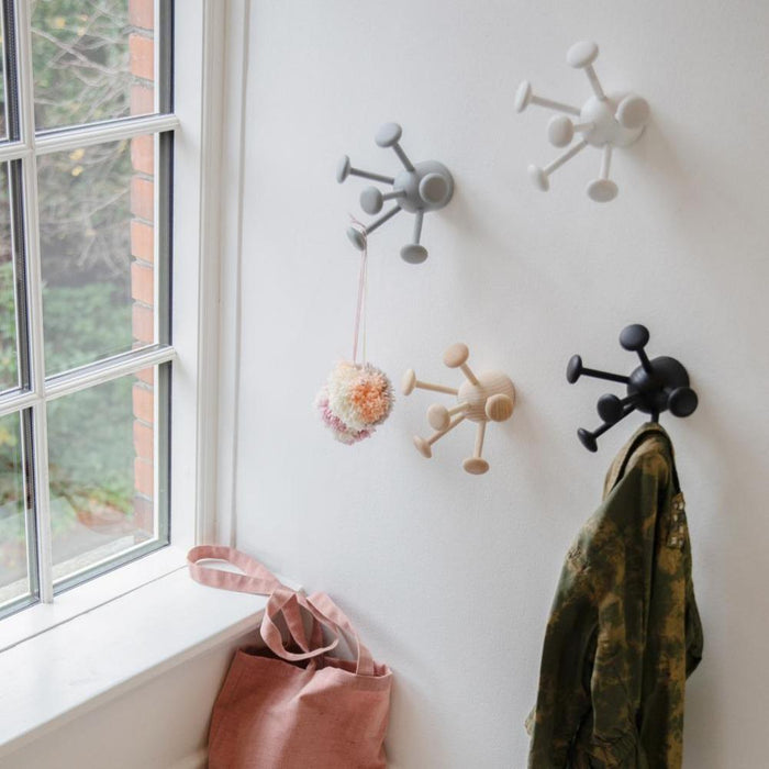 Wall with four eigt-armed hooks, in grey, white, black and natural ash wood, a light pink cotton bag placed on a bench beneath