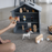 Child playing with grey doll's house inhabited by small toy figures and toy cars