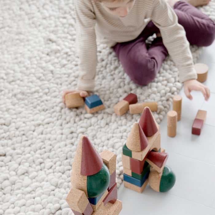Boy sits on carpet and plays with building blocks   shaped like cones, squares, trapezes, cylinders and   rectangles and balls.