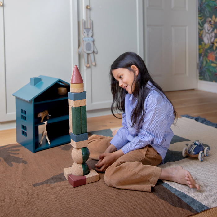 Girl sits on carpet and builds tall tower of bricks   in various shapes and sizes.