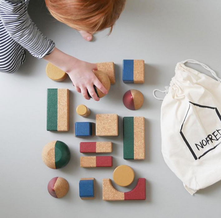 Child lining up 18 building blocks beside an   organic cotton bag with Nofred logo printed on.
