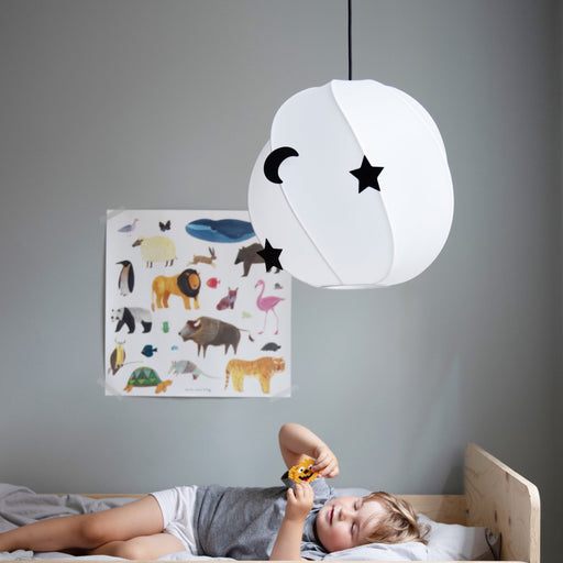 Kids room with white loft lamp, wooden bed and a boy lying in bed holding a piece of toy, poster with drawed animals hanging on the grey painted wall in the background.