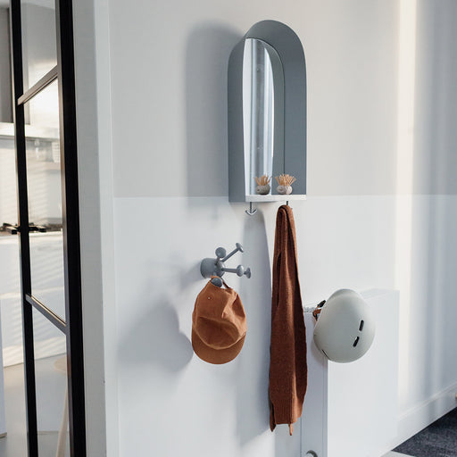 Kids mirror hanging on the wall in the family hallway, the frame is grey ith a wooden shelf, and from the two hooks hangs a white cycling helmet , a scarf and a cap