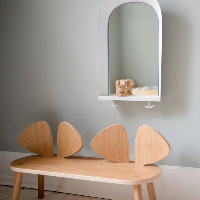 Bench for kids in wood, placed underneath mirror with small wooden toy dog on the shelf