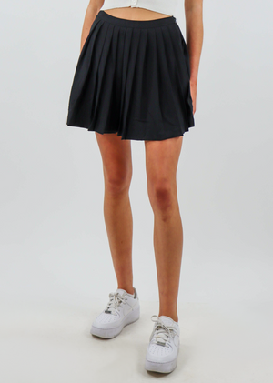 black mini tennis skirt with pleating throughout the body and invisible zipper