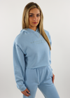 "Light Blue Baby Blue Comfy Cozy Soft Cropped Hoodie with Embroidered Logo on Right Wrist and the Quote ""We all need something to believe in so look in the mirror"" Embroidered on the Front Center."