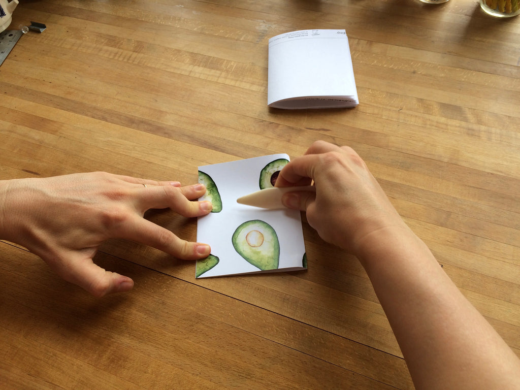 hands folding paper in half with paper creaser
