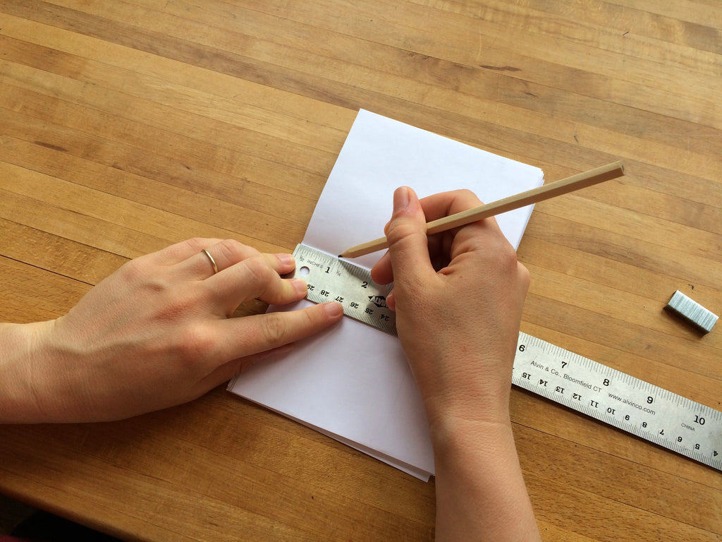 using a ruler to measure and make marks on a stack of paper