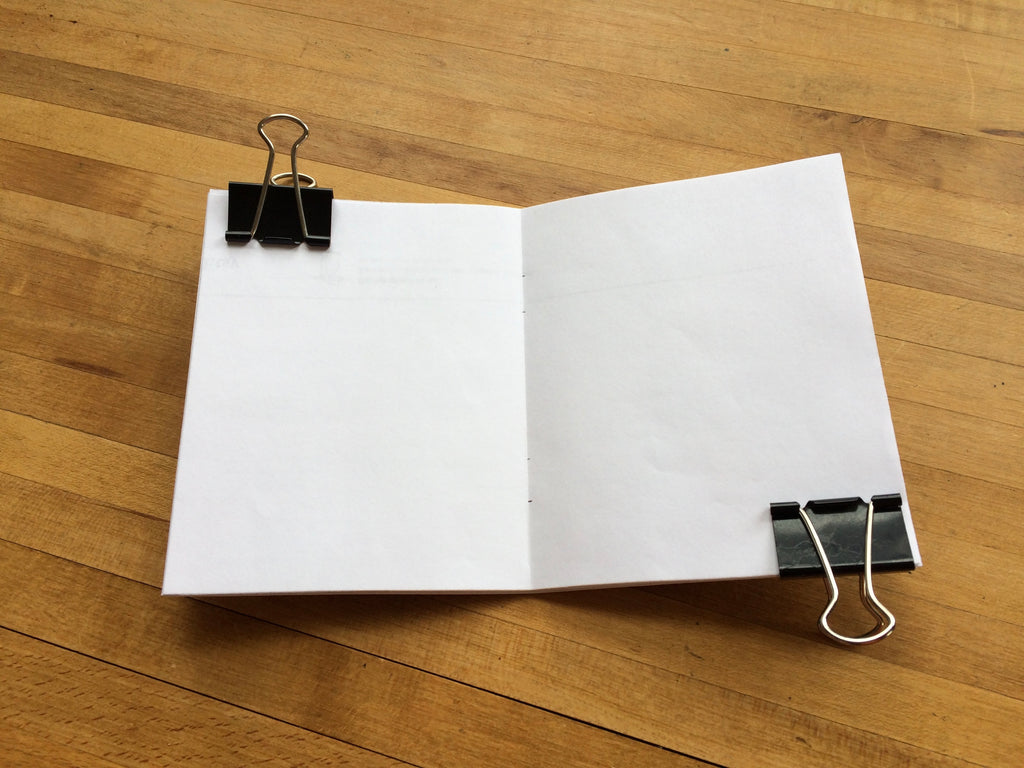 A stack of paper clipped together with binder clips at each end