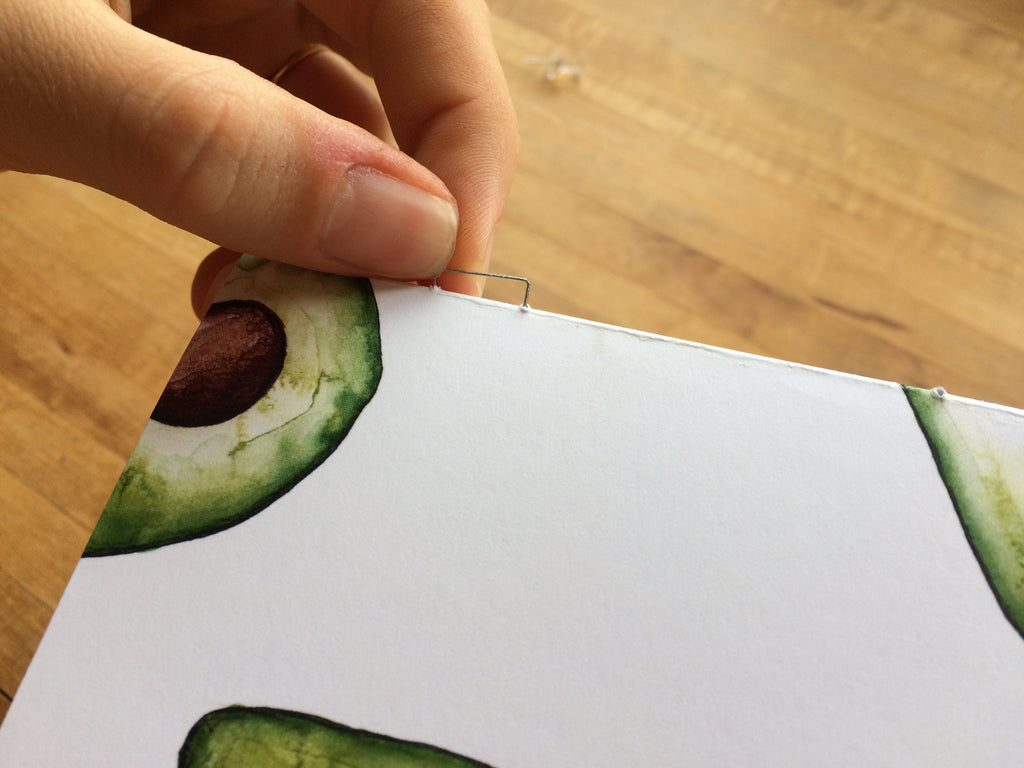 hand pushing a staple into a stack of paper