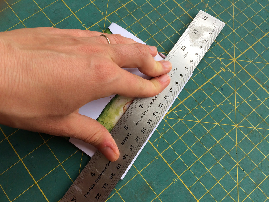 handing holding ruler against edge of notebook