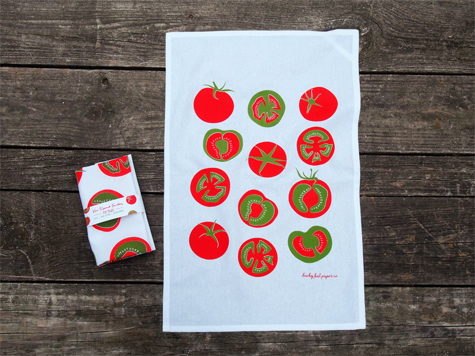 white tea towel with a tomato pattern on a picnic table