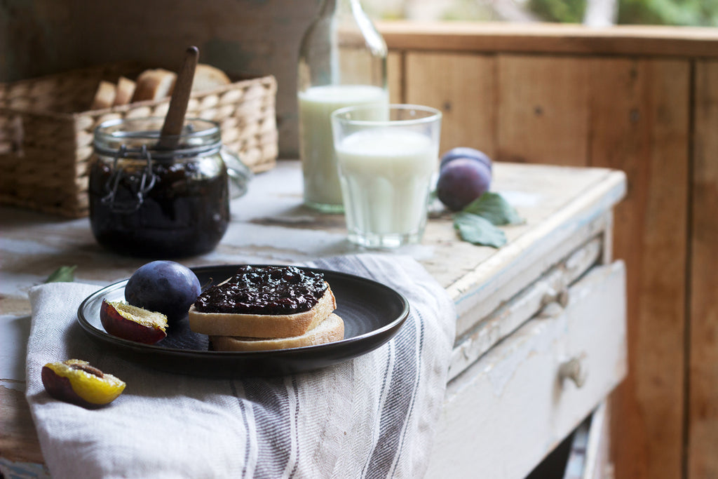 toast with plum jam served with milk sitting on a wooden bench with a tea towel