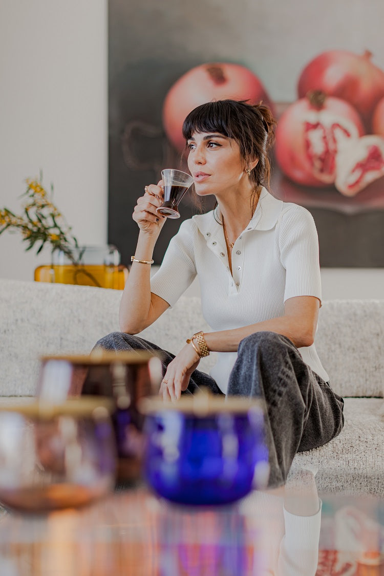 Nur Bilen Yavuzer , Founder & Creative Director of @beautyomelette, drinking coffee from NUDE Addict glass with the NUDE Beret collection presented in front of her on the table
