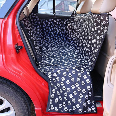 An image of a black waterproof seat cover from Petslop covered in white paw prints and filling the backseat of a red car.