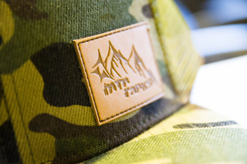 leather patch with mountain design on camo hat