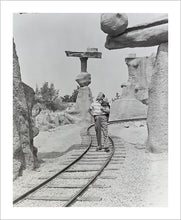 "Load image into Gallery viewer, ""Walt Walking on the Tracks of Rainbow Caverns Mine Train"" from Disney Photo Archives"